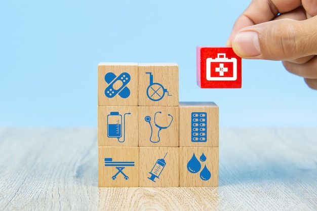 De close-uphand kiest gezondheidszorg en medische symbolen op houten die blokkenstuk speelgoed voor zorgverzekeringsconcepten wordt gestapeld.