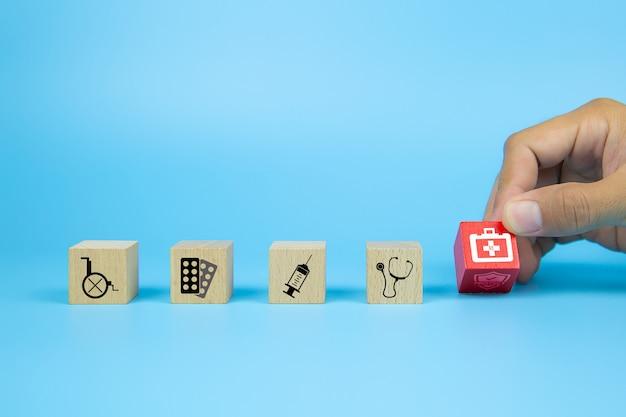 De close-uphand kiest kubus houten speelgoed blokken die met het pictogram van de eerste hulpuitrusting worden gestapeld voor gezondheidszorg en medisch.