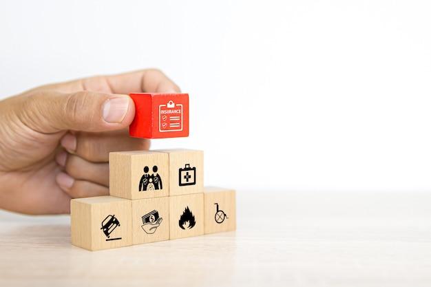 De close-uphand kiest kubus houten stuk speelgoed blok met verzekeringspictogram.