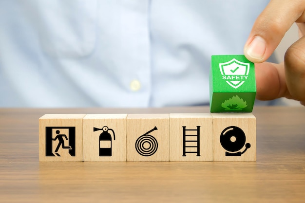 De close-uphand kiest verhinder symbool op houten kubusblokken gestapeld met nooduitgangpictogram