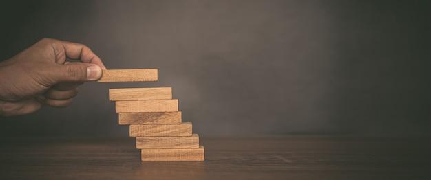 De close-uphand plaatst houtbloktoren die in tredestap wordt gestapeld.