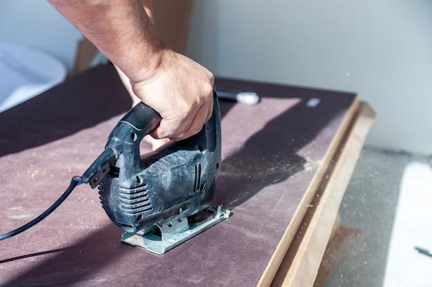 De close-uphand van arbeider met professioneel scherp hulpmiddel, sneed houten tafelblad