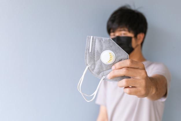 De close-uphand van de jonge mens geeft een masker tegen besmettelijk coronavirus en pm2.5-stof