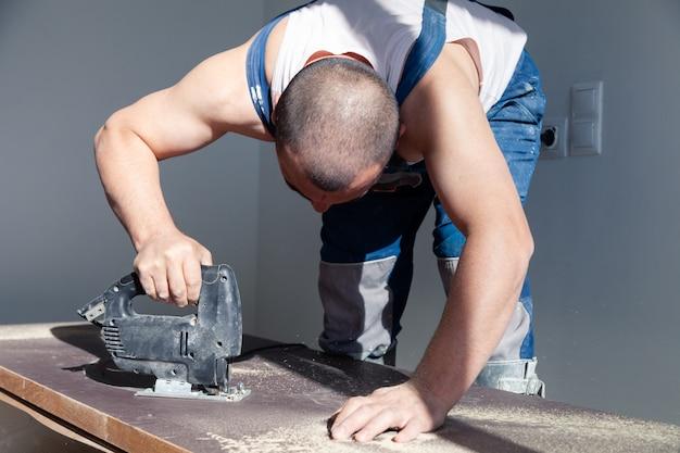 De close-uphand van timmerman, schrijnwerker met professionele snijgereedschapzaag of figuurzaag, sneed houten tafelblad, zaagende plank, het bruine indienen, zaagsel. timmerwerkplaats, handarbeid