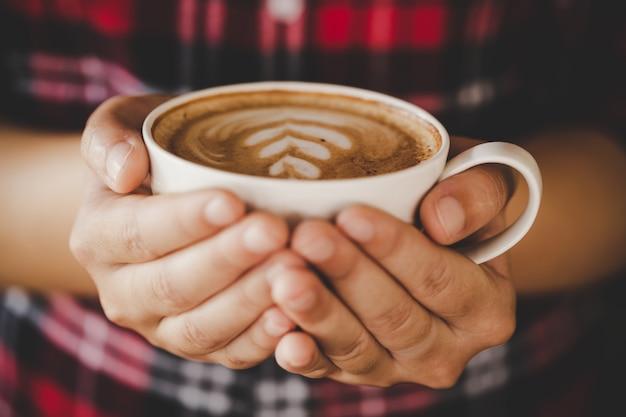 De close-uphand van wijfje die een koffiekop in de koffie houden voegt de toon van de filter retro kleur toe