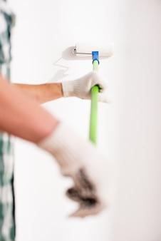 De close-uphanden van de jonge mens doen thuis reparatie.