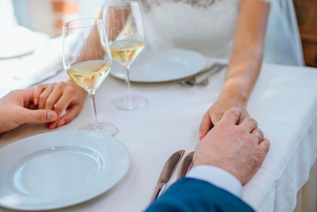 De close-upjonggehuwden houden elkaars hand bij een lijst in restaurant met twee glazen wijn