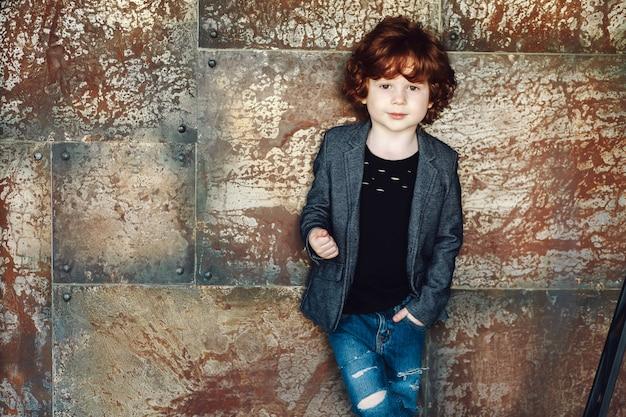 De close-upmening van een krullende jongen met bruine ogen kleedde omhoog jasje, zwart overhemd en gescheurde jeans