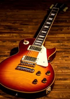 De close-upmening van het elektrische gitaarlichaam is op de houten vloer