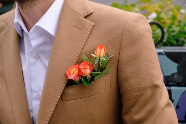 De close-upmens kleedde zich in elegante jaket met drie rozen in poket