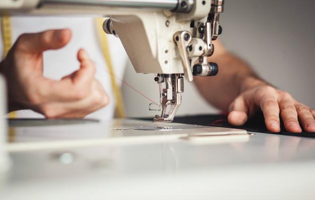 De close-upmens overhandigt naaiende stof op naaimachine