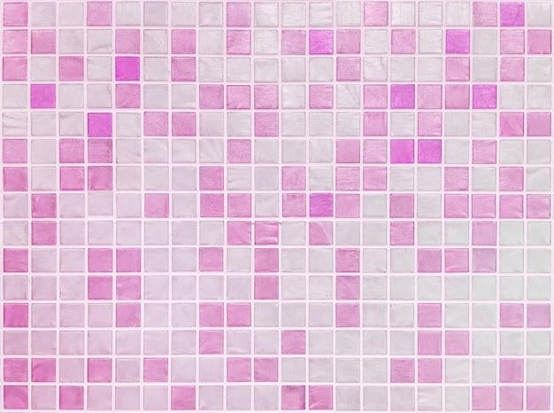 De close-upoppervlakte betegelt patroon bij roze tegels op de textuurachtergrond van de badkamersmuur