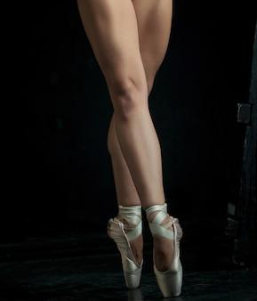 De close-upvoeten van jonge ballerina in pointe-schoenen tegen de zwarte achtergrond