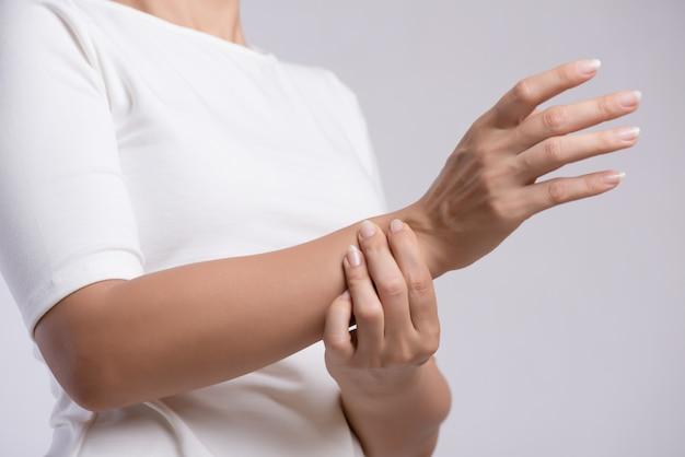 De close-upvrouw houdt haar verwonding van de polshand, voelend pijn. gezondheidszorg concept.
