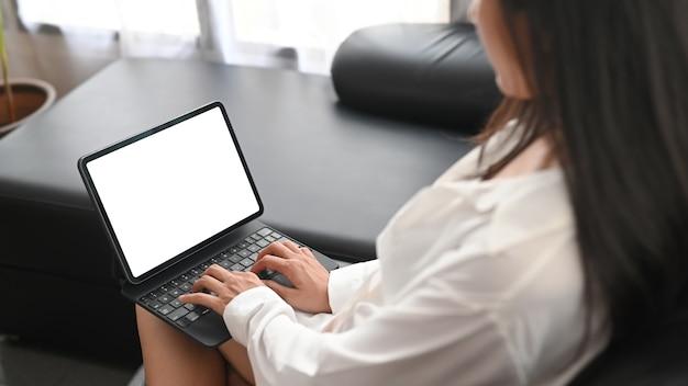 De close-upvrouw in pyjama's gebruikt een computertablet op de zwarte bank.