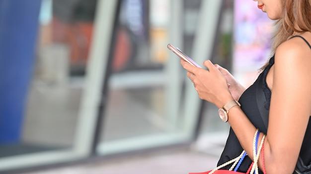 De close-upvrouw in zwart hemd die smartphone gebruiken terwijl status met het dragen van het winkelen doet na het winkelen bij het stedelijke winkelcentrum met vage ingang in zakken