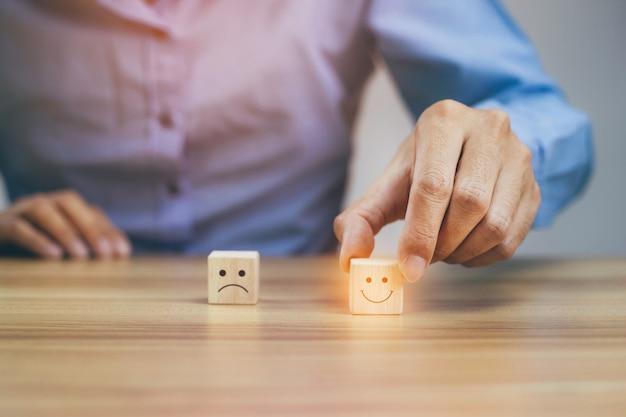 De close-upzakenman kiest smileygezicht en wazig droevig gezichtspictogram op houten kubus