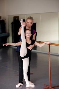 De coach leert het meisje hoe ze de choreografie moet uitrekken