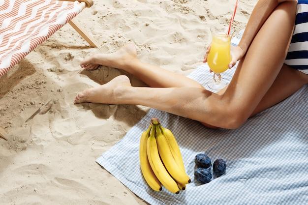 De cocktail van de vrouwenholding terwijl het rusten bij kust in hete zonnige dag