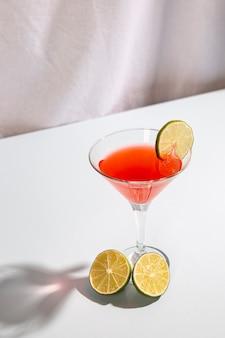 De cocktaildrank versiert met citroen over witte lijst