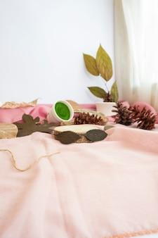 De compositie geeft het product weer. oud hout versierd met gedroogde bladeren en doek. minimalistische compositie met producten