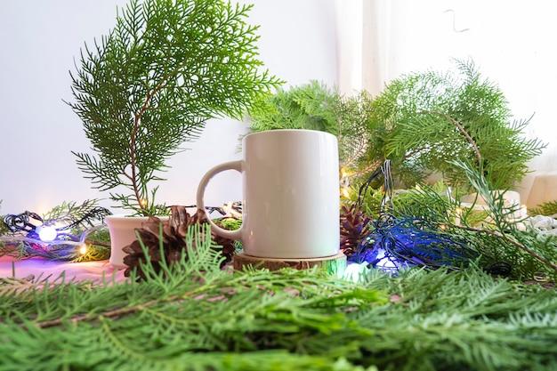 De compositie geeft het product weer. witte mok op oud rond hout met decoratie van dennenbladeren. ideeën voor het weergeven van zomerproducten