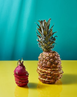 De compositie met enkel tropisch exotisch fruit ananas en drakenfruit, pitaya opgebouwd uit plakjes op een duotoon geelgroene achtergrond.