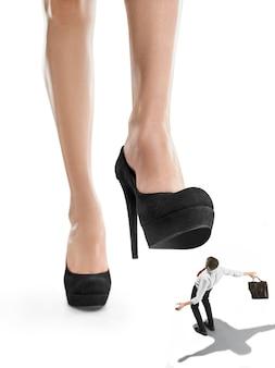 De conceptuele collage over vrouwelijke baas en kleine man onder grote vrouwelijke hiel. het concept van onderdrukking en angst.