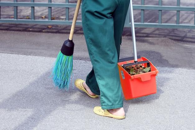De conciërge veegde de stoep van de stad van de gevallen bladeren. werk op het gebied van straatreiniging