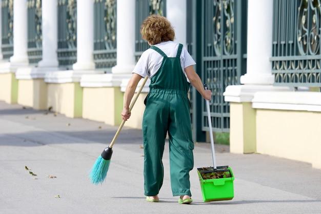 De conciërgevrouw reinigt de stoep van de stad van gevallen bladeren. werk op het gebied van straatreiniging