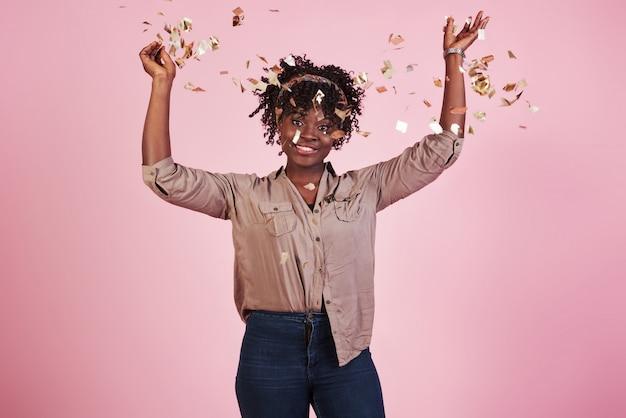De confetti in de lucht gooien. afrikaanse amerikaanse vrouw met roze erachter achtergrond