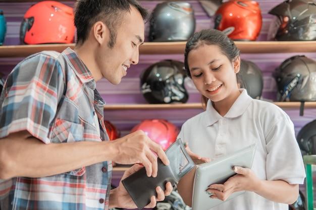 De consument heeft een portemonnee om te betalen wanneer hij wordt bediend door een winkelier met een tablet in een helmwinkel