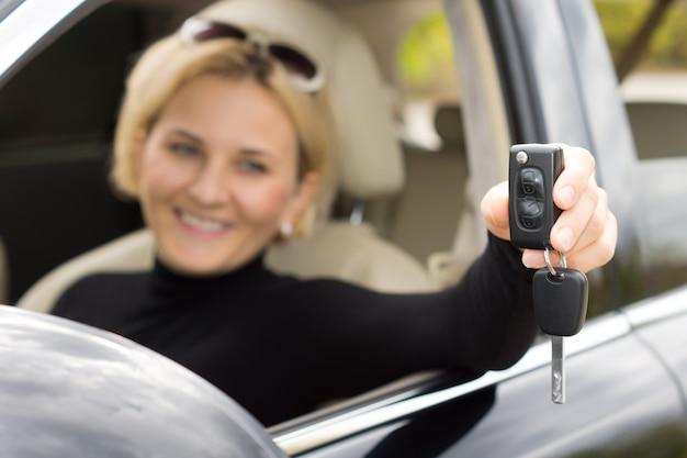 De contactsleutel van de auto en de afstandsbediening worden uit het open raam gehouden