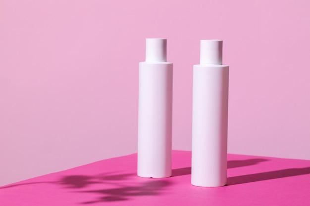 De containers van huidverzorgingsproducten op heldere roze achtergrond sluiten omhoog