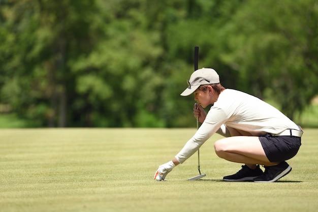 De controlelijn van de vrouwengolfspeler voor het zetten van golfbal op groen gras