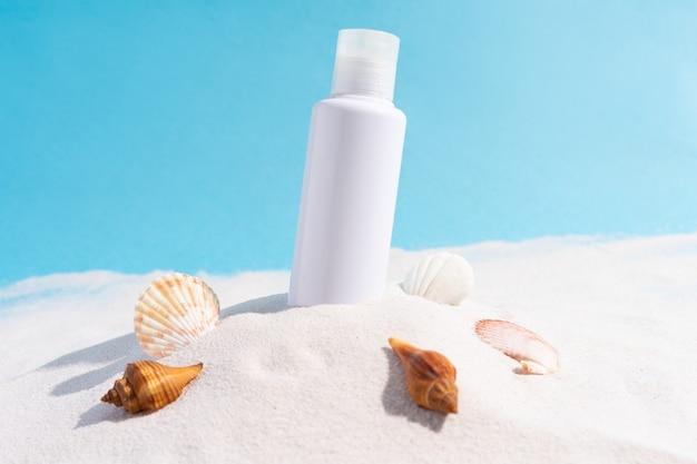 De cosmetische fles wordt op het zand geplakt met schelpen eromheen