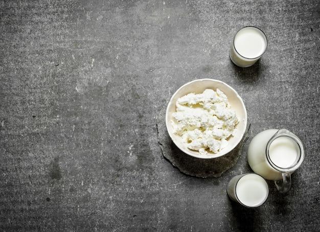 De cottage cheese in een kom en melk op de stenen tafel