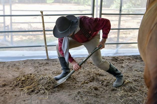 De cowboy man ruimt de stallen op zijn boerderij op.