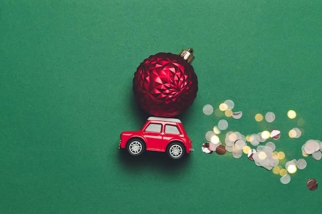 De creatieve kerstmissamenstelling met een rode stuk speelgoed auto met een kerstmisbal op de kap en fonkelt snoep op een groene achtergrond met compise. platliggend, minimale stijl