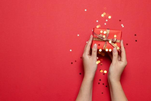 De creatieve samenstelling die van vrouwelijke handen een rood giftvakje met boog houden en schittert stersuikergoed op een rode achtergrond met plaats voor tekst