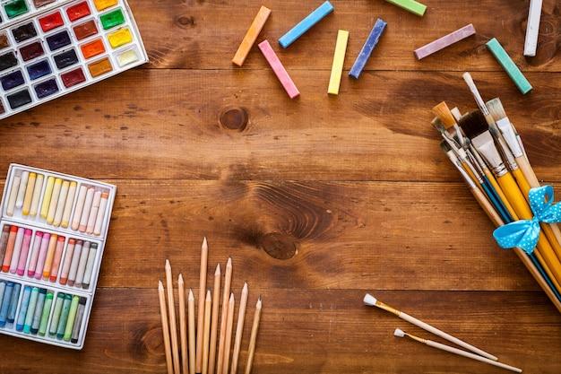De creatieve toebehoren van het kunstwerk op bruine houten vlakke achtergrond, leggen, exemplaarruimte