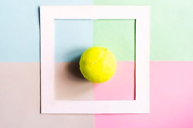 De creatieve vlakte lag met tennisbal die in wit kader op kleurenachtergrond wordt geïsoleerd, creatief ideeconcept f