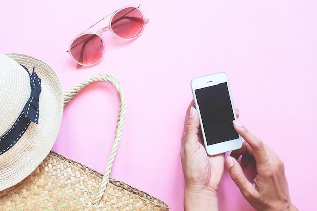 De creatieve vlakte legt van de zomerinzameling met vrouwenhand gebruikend smartphone op kleurenachtergrond
