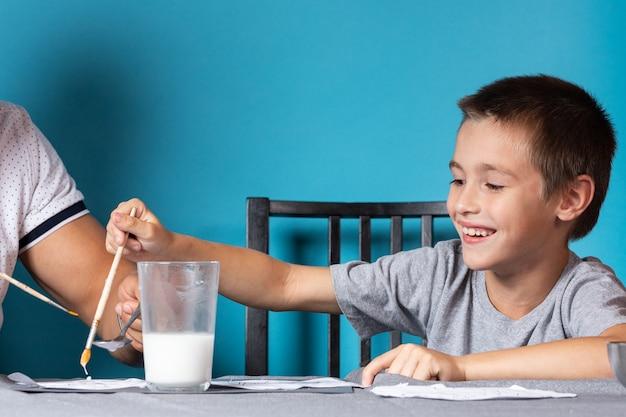 De creativiteit van kinderen. vader en zoon schilderen met verf op blauwe achtergrond