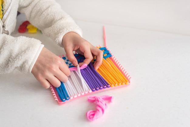 De creativiteit van kinderen weven met gekleurde dradenkabels