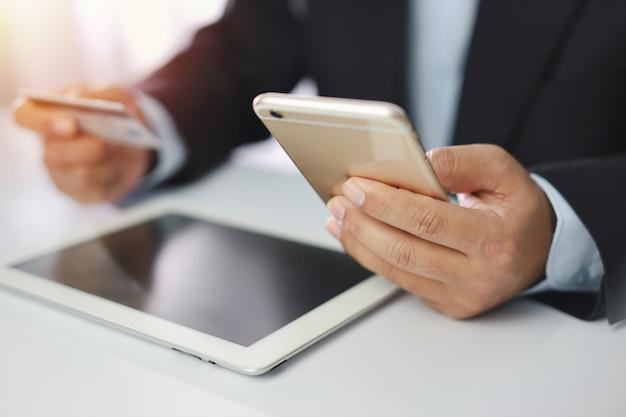 De creditcard en de smartphone van de zakenmanholding