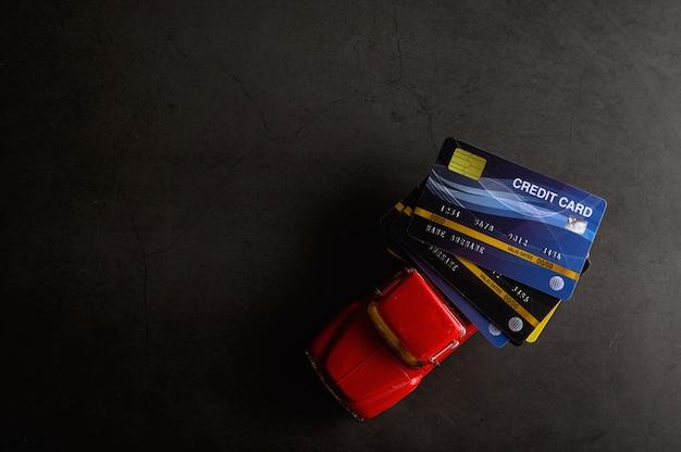 De creditcard op het rode pick-upmodel op de zwarte vloer