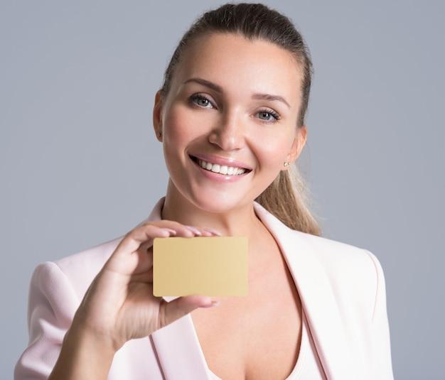 De creditcard van de bedrijfsvrouwenholding tegen haar gezicht geïsoleerd studioportret