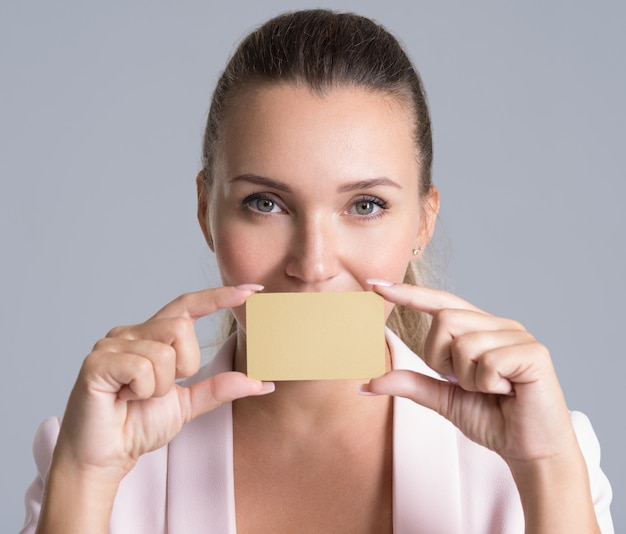 De creditcard van de bedrijfsvrouwenholding tegen haar lippen geïsoleerd studioportret