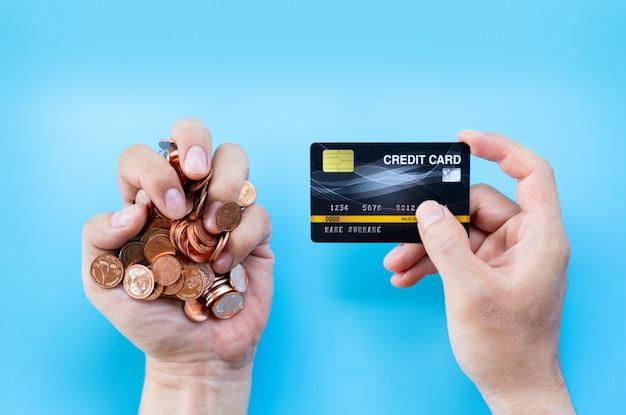 De creditcard van de handgreep en muntstuk of contant geldachtergrond